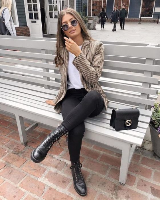 Girl wearing ankle boots and black jeans, white blouse and sand-colored blazer