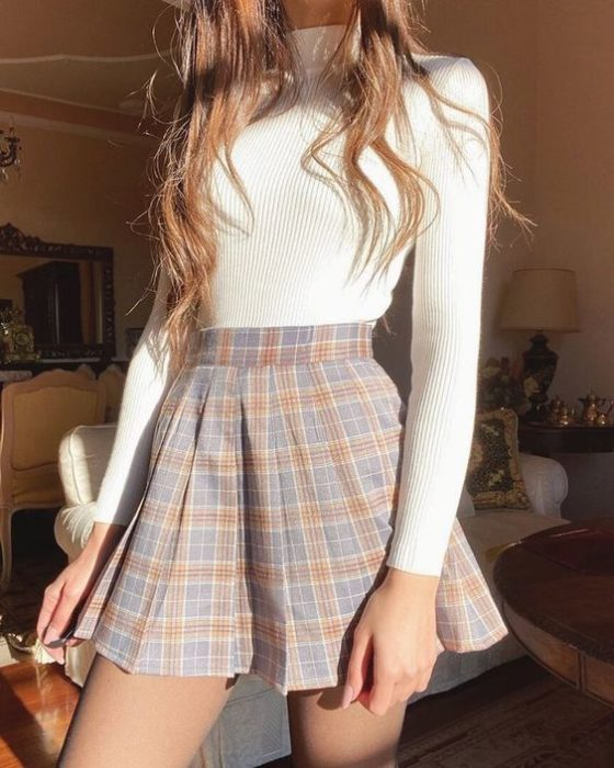 Girl wearing mini skirt with tartan print in blue and brick tones and long-sleeved blouse and high neck in white
