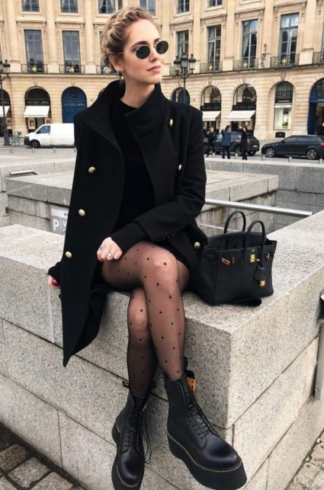 Girl wearing a total black look, dress, coat, stockings and ankle boots