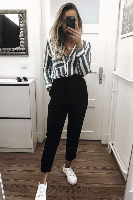 Girl wearing loose white and green striped shirt, black straight waist pants and white tennis shoes
