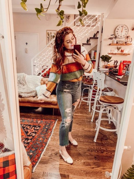 Curvy girl wearing ballerinas, ripped jeans, and striped sweater in fall colors