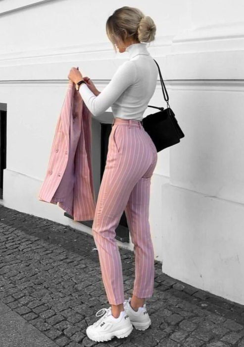 Girl wearing baby pink outfit, tennis shoes and long-sleeved, high-neck white blouse