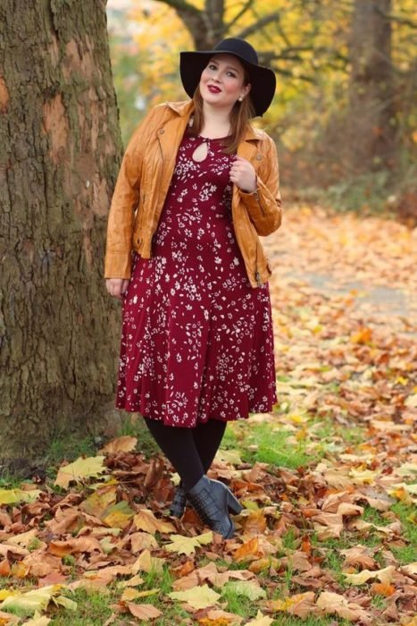 Curvy girl wearing gray ankle boots, black tights and hat, wine colored midi dress and flower print and mustard jacket