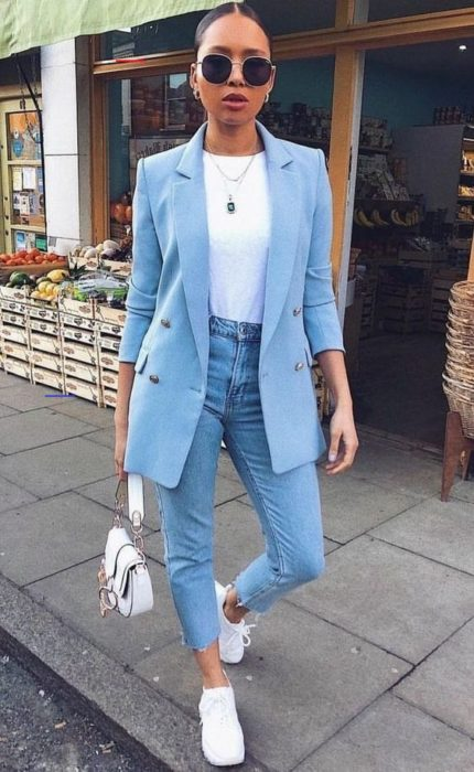 Girl wearing denim jeans, white blouse, sky blue blazer and white tennis shoes