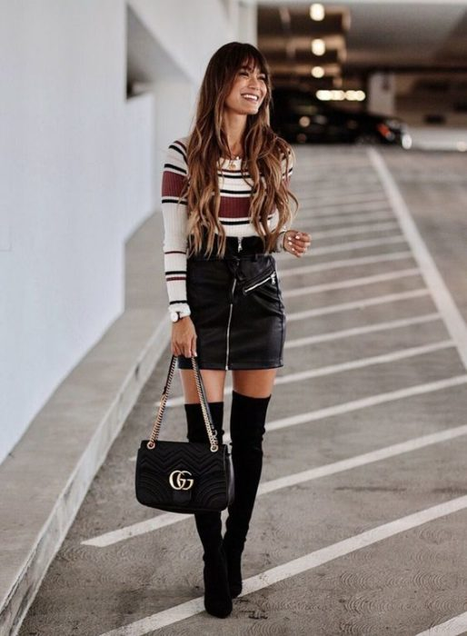 Girl in white blouse and red stripes and black skirt with long boots