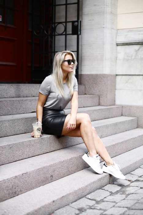 Blonde girl with loose hair wearing gray blouse, black dalda and white tennis shoes