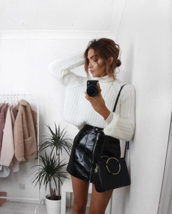 Girl taking a selfie in white sweater and black skirt