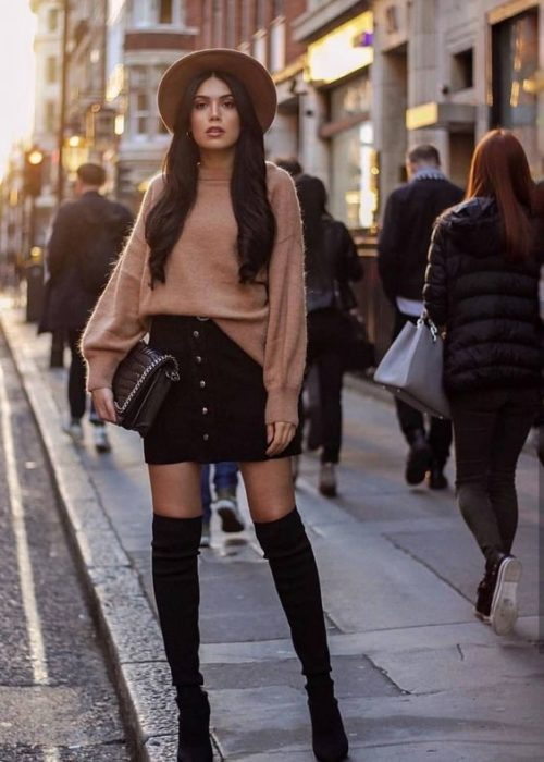 Girl with long flowing hair in black skirt, high boots and beige sweater