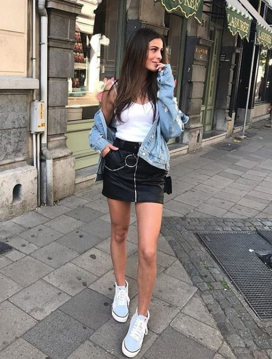 Girl with long loose hair in white blouse, denim jacket and black skirt