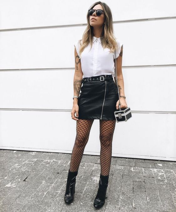 Blonde girl with loose hair wearing white blouse, black miniskirt, stockings and booties