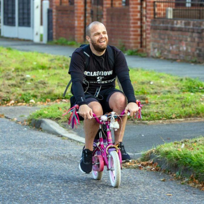 Hombre pedaleando en una bicicleta rosa