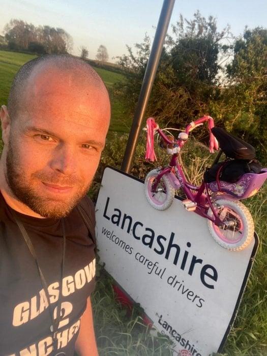 Hombre tomando una selfie con una bicicleta rosa