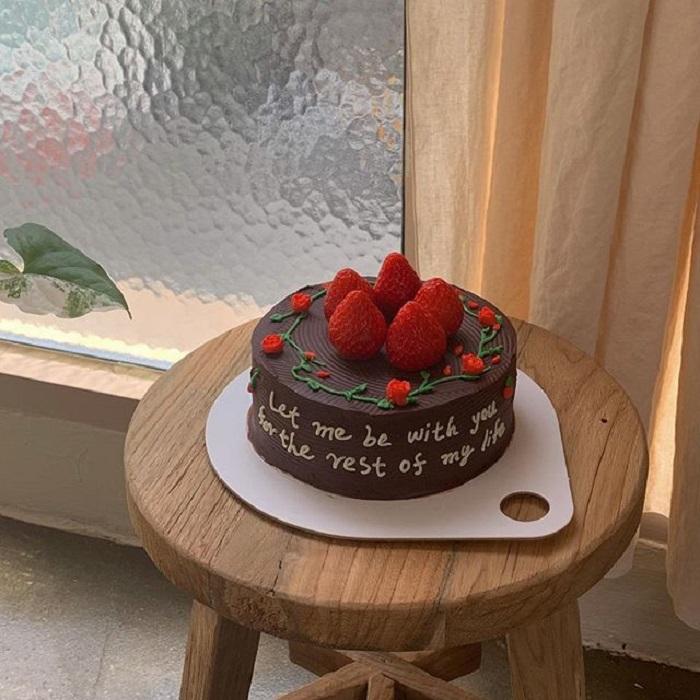 Pastel de la repostera Koike, de chocolate, con fresas y rosas pequeñas, además de una frase en color blanco
