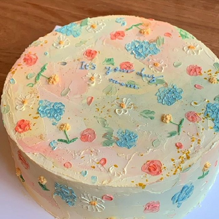 Pastel de la repostera Koike, en colores pastel, fondo beige,  detalles azules, rosas y amarillos