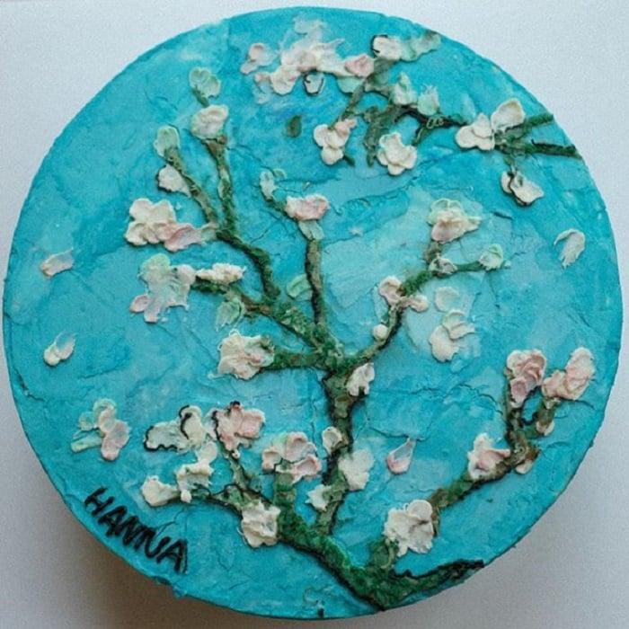 Pastel de la repostera Koike, de fondo azul y árbol de cerezo con flores blancas