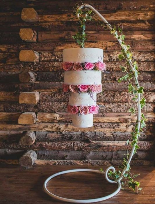 Pastel de bodas volteado pendiendo de un  armazón