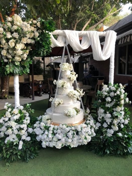 Pastel de bodas de cuatro pisos montado en un columpio