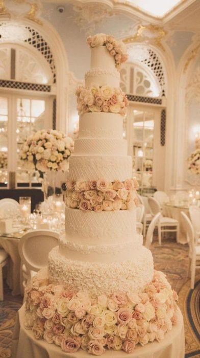 Pastel de bodas de seis pisos con decorado de rosas