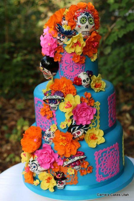 Pastel inspirado en el Día de muertos de tres pisos en color verde con flores de betún