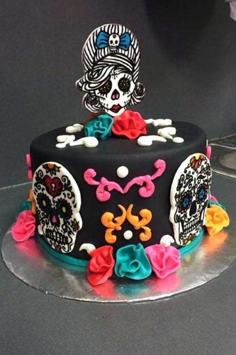 Pastel inspirado en el Día de muertos en color negro con galletas de mantequilla en forma de calavera