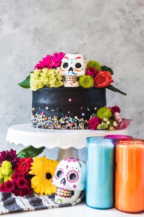 Pastel inspirado en el Día de muertos d eun piso en color negro con confitería
