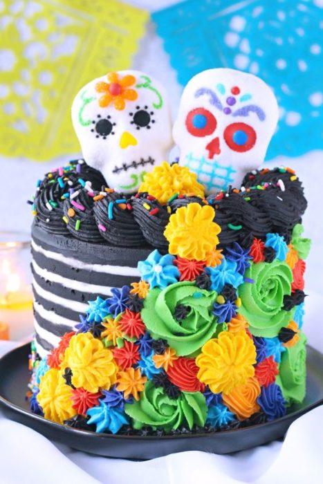 Pastel inspirado en el Día de muertos en color negro con líneas de betún blanco