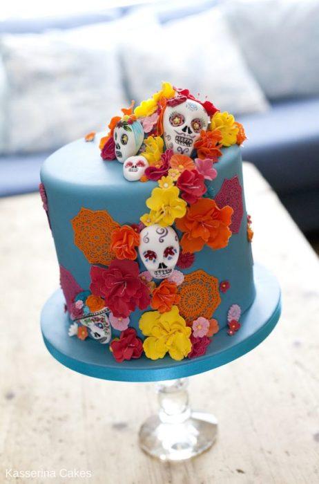 Pastel inspirado en el Día de muertos en color azul con calaveras de dulce miniatura