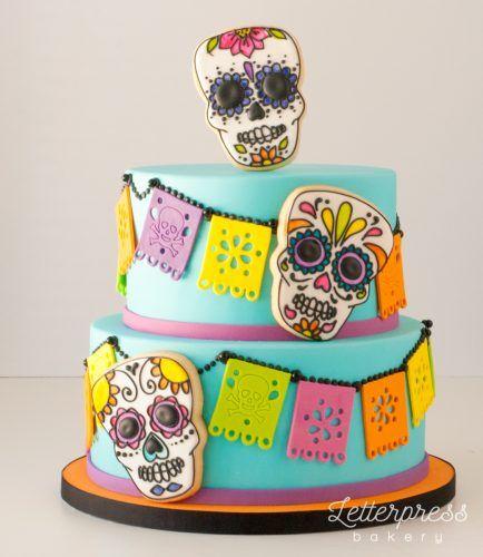 Pastel inspirado en el Día de muertos en color aguamarina de dos pisos con decoración de calaveras