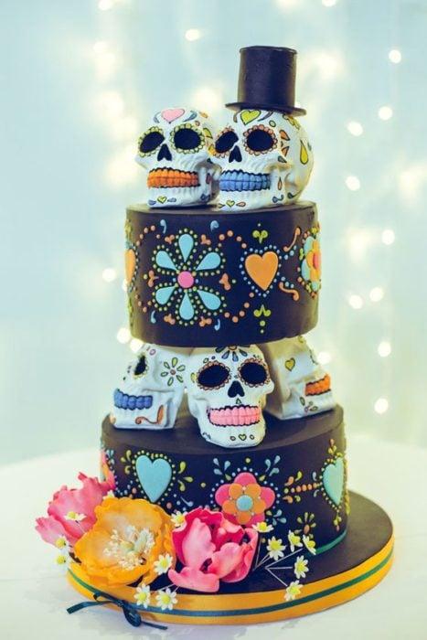 Pastel inspirado en el Día de muertos de dos pisos con calaveras de dulce