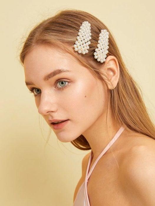 Chica peinada con broches en los lados con perlitas