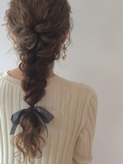 Girl with wavy hair, in full braid with a ribbon bow at the end of this