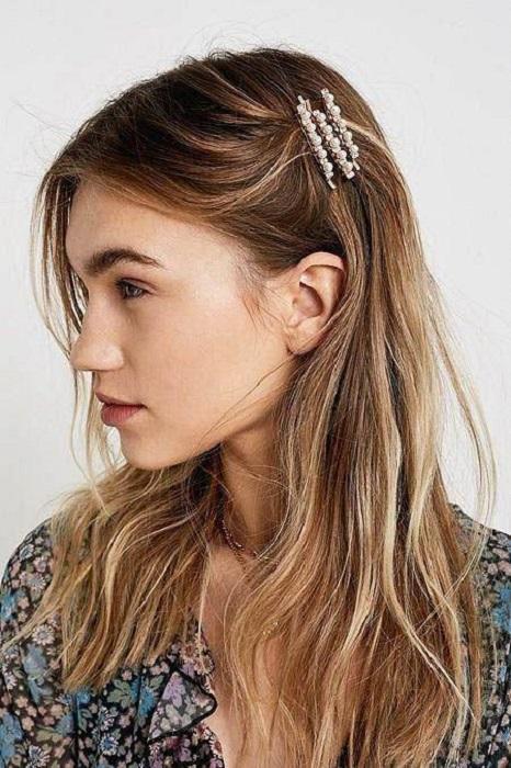 Chica peinada de lado con pasadores con perlitas