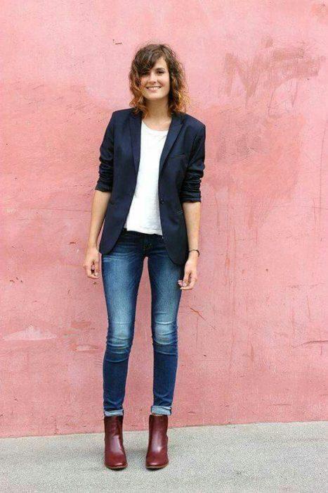 Mujer con cabello castaña corto, jeans, botines cafés, blusa blanca y saco negro