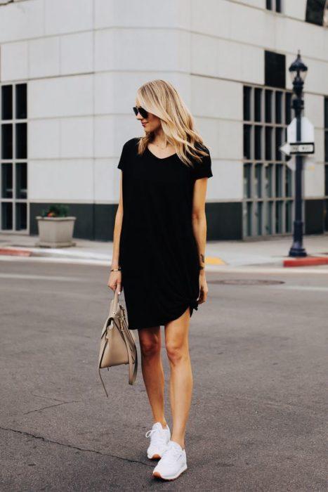Chica rubia con vestido negro suelto y tenis blancos