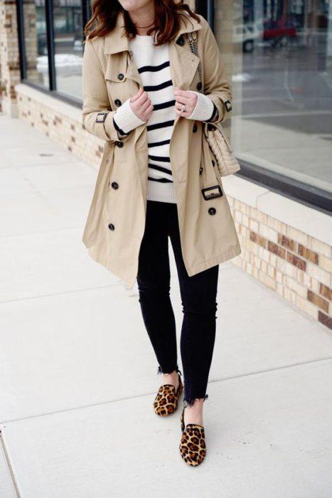 Chica con suéter de blanco con rayas negras, gabardina beige y pantalones negros