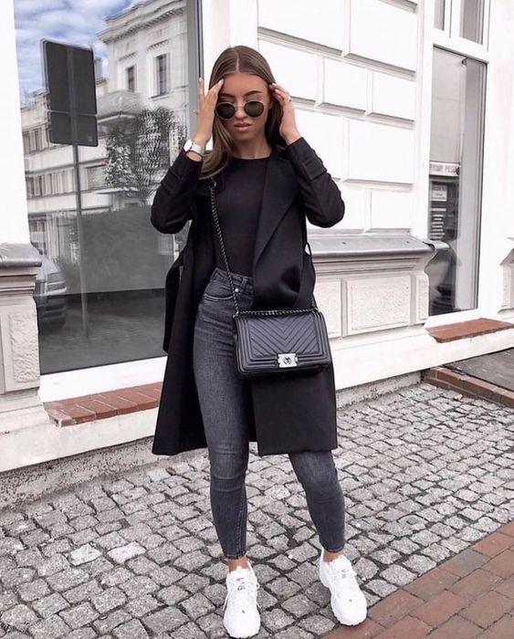 Chica de cabello largo suelto con jeans oscuros, blusa negra, saco negro y tenis blancos
