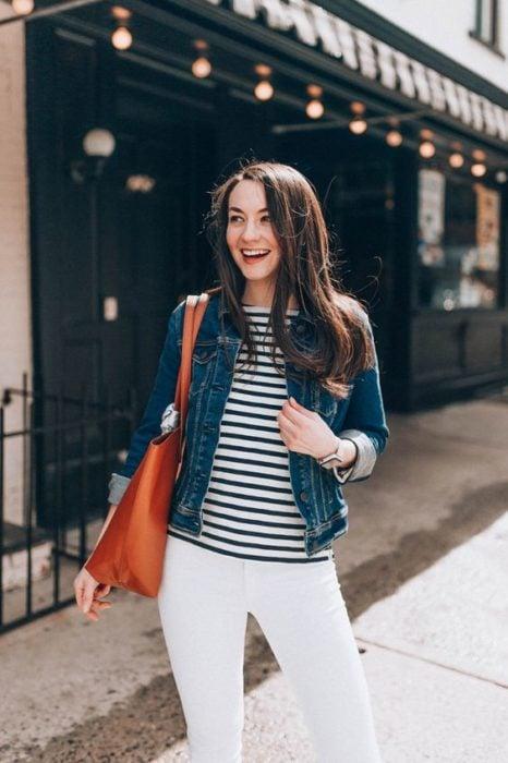 Chica de cabello largo oscuro con blusa de rayas, pantalón blanco y chamarra de mezclilla