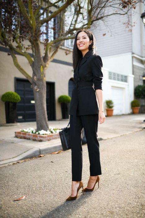 Chica delgada con blusa y pantalón de vestir negros