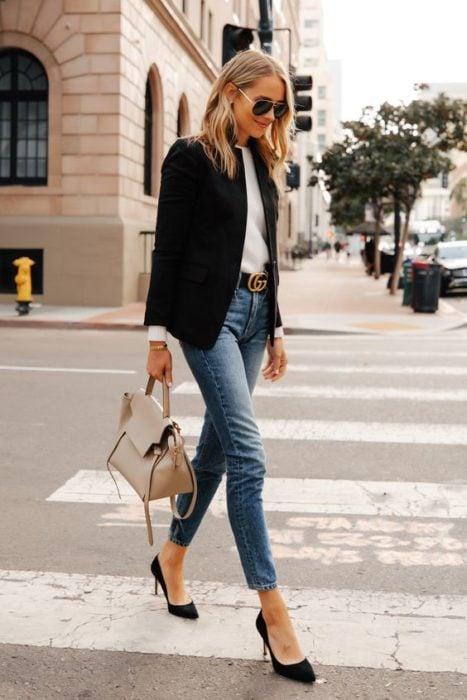 Chica rubia con jens, blusa blanca, tacones negros y saco negro