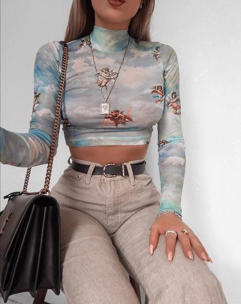 Chica delgada con crop top de manga larga color azul con estampado de ángeles y pantalón beige