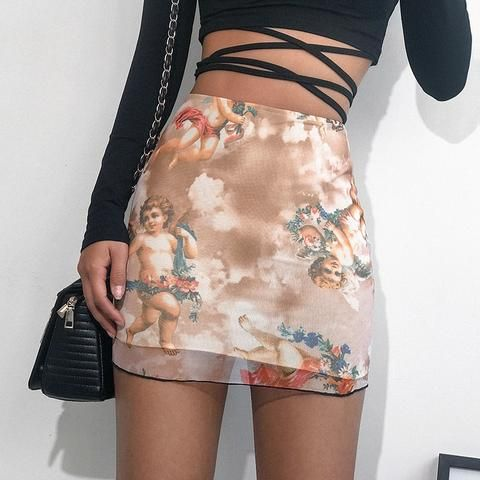 Chica delgada con crop top con tiras en la cintura con falda café con beige con estampado de ángeles