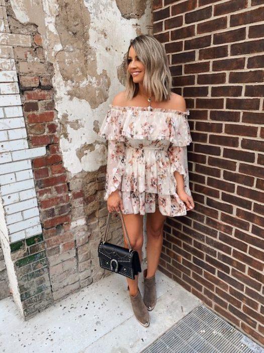 Chica rubia con melena corta con vestido blanco con flores lleno de olanes