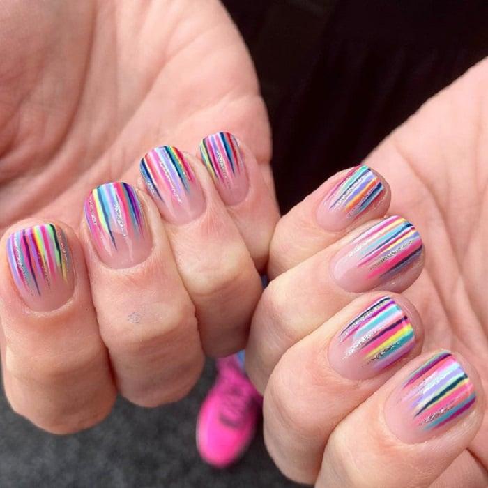 Nail art serpentina en tonos arcoíris con brillo