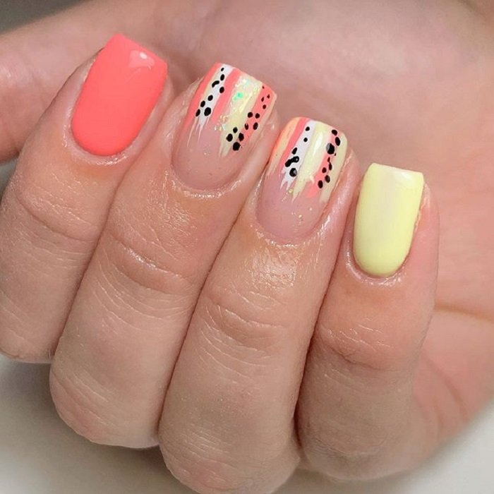 Serpentine nail art in coral and yellow tones with black details