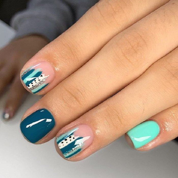 Serpentine nail art in green, blue and mint tones