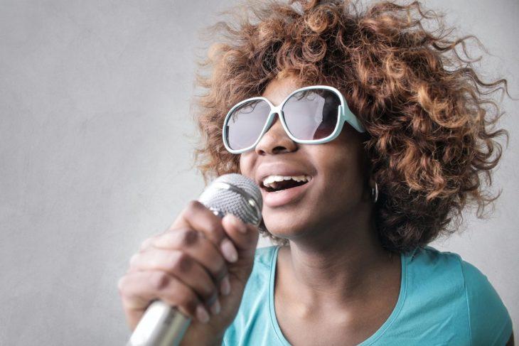 Chica de tez morena con micrófono cantando y usando lentes oscuros