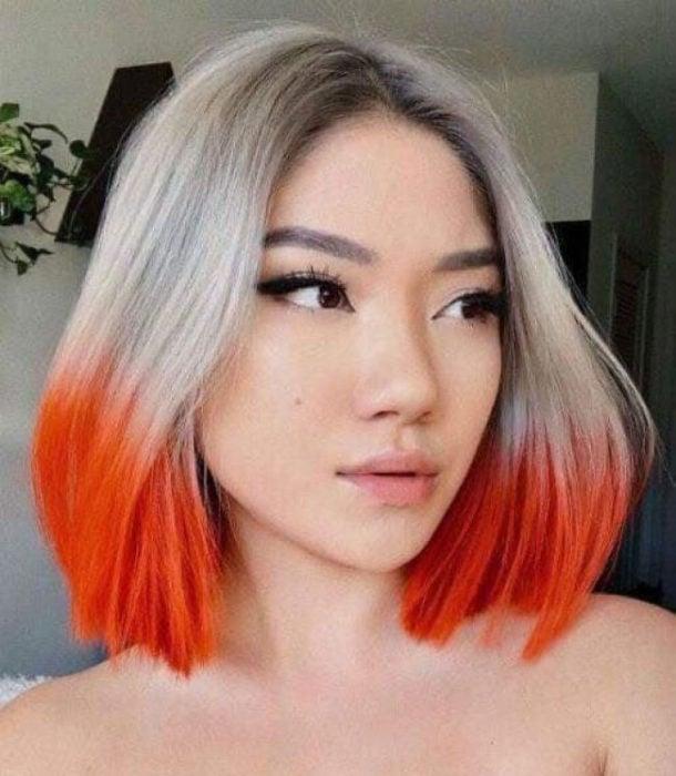 Chica con el cabello teñido en platinado con las puntas en color naranja