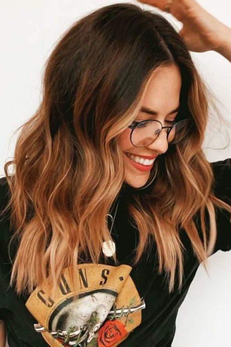 Chica con el cabello color café con luces en color dorado