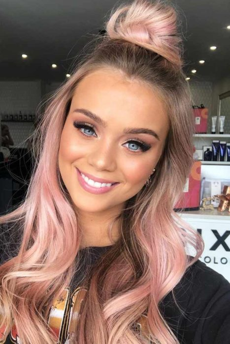 Chica con el cabello teñido de color rosa con un half bun