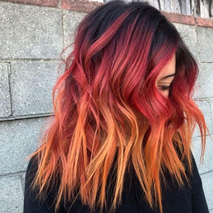 Chica con el cabello teñido de color rojo con las puntas en color amarillo